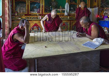 Diskit, India - August 20, 2015: Buddhist monks working on a mandala in monastery prayer hall. A mandala is a spiritual and ritual symbol in Indian religions, representing the universe