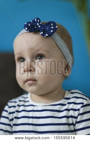Portrait of an adorable little girl with headband ashamed expression