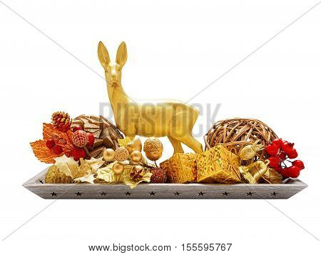 Golden deer surrounded by Christmas decorations on wooden tray isolated