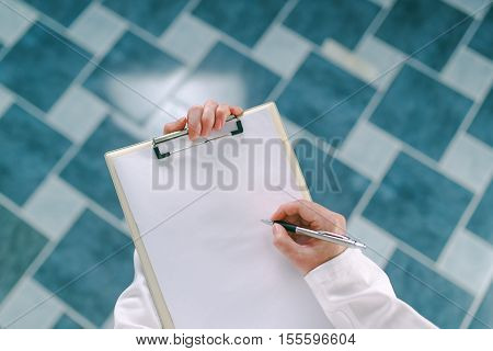 Female doctor in white uniform writing on clipboard paper medicine prescription. Woman as health specialist in exam er disease prevention visit check or healthcare lifestyle concept