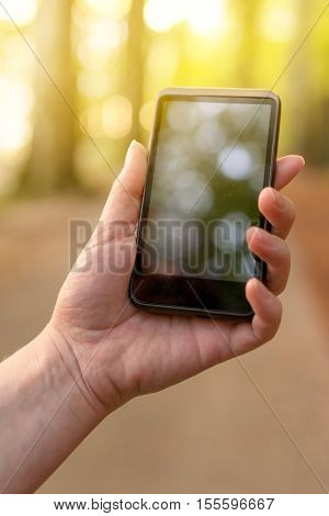 Searching for gsm signal in the forest female hand holding mobile phone high up and trying to find network