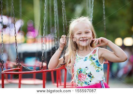 Cute little girl enjoing time at fun fair, chain swing ride, amusement park in summer