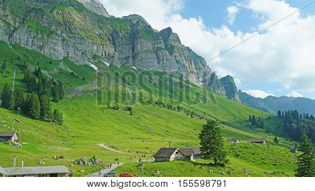 The Alpstein-massif in the Swiss Mountains, green mountain meadows with small huts, hiking trails, blue sky and white clouds