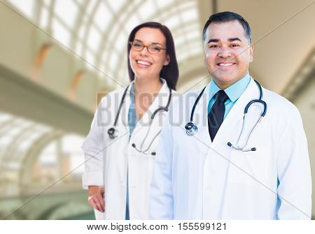 Two Male and Female Doctors or Nurses Standing Inside Hospital Building.