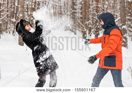 Young couple playing in snow, having snowball fight.