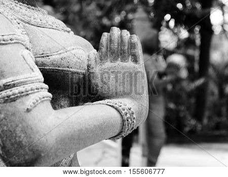 stone statue of indian woman helds her hands together in namaste