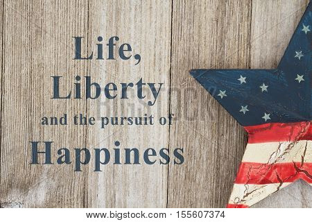 USA patriotic message USA patriotic old flag on a star with weathered wood background with text Life Liberty and the pursuit of Happiness