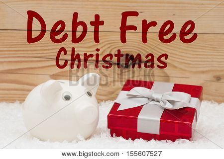 Saving at Christmas Time A white piggy bank with a red Christmas present on snow and a weathered wood background with text Debt Free Christmas
