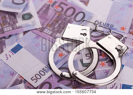 Pair Of Handcuffs Closeup On Euro Banknotes Background