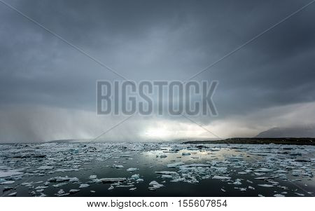 Icebergs on the shore of Jokulsarlon glacier lagoon with storm approaching