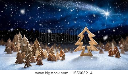 Wooden decoration arranged in snow forming a fantasy forest night landscape with a shooting star ideal for Christmas or winter