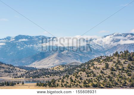 Clouds on top of mountains in valley of Mount Shasta in northern California with pine trees on hills