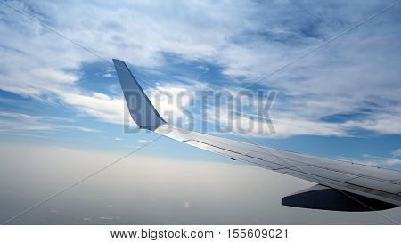 Airplane wingon the sky with fluffy clouds