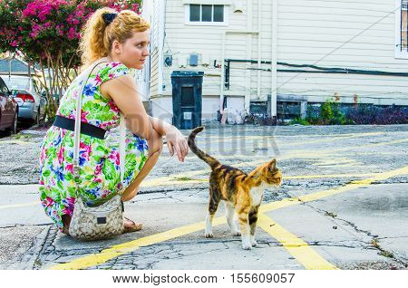 Young woman with stray thin calico cat on street of New Orleans