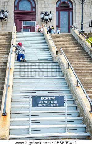 Montreal, Canada - July 25, 2014: Person praying on steps of Saint Joseph's Oratory of Mount Royal with sign