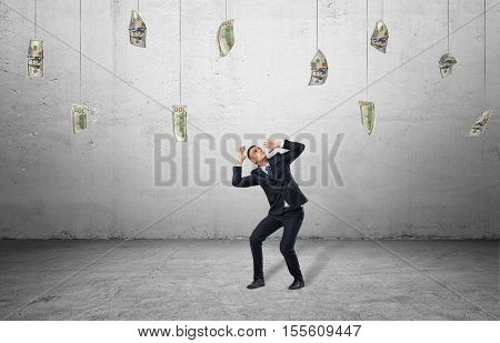 A scared businessman in a protective pose with loads of money hanging in the air on the background of the grey wall. Business and finance. Corruption. Earning money.