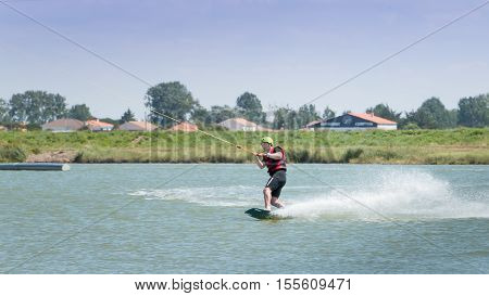 Aiguillon-sur-Mer France France - July 06 2016 : installing a wake park during the 2016 season on the Lake of Aiguillon sur Mer France - wakeboarder is exerted on the lake to make figures
