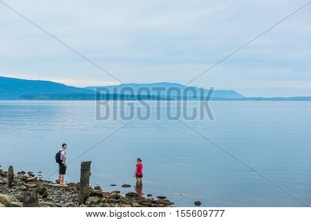 Bellingham, USA - April 3, 2016: Calm blue bay in Washington during sunset with people relaxing by water
