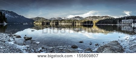 Eibsee lake winter panorama - Panorama image with the lake Eibsee and its icy shore near the municipality Grainau in the district of Garmisch-Partenkirchen in Bavaria Germany