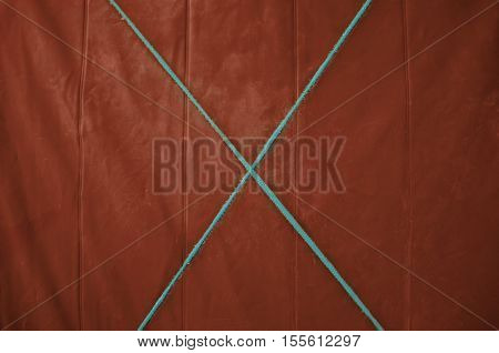 Texture red tarp with a blue cross in the middle of the rope. Yellow background.