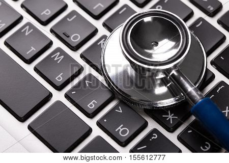 Stethoscope on laptop keyboard closeup. Computer service