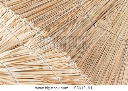 Straw beach umbrella close up. Woven straw background.