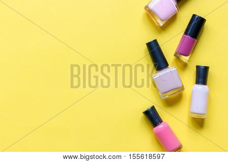 lot of bottles of nail polish on yellow background top view