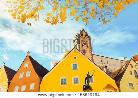 Old buildings of Fussen city. Fall season scene with yellow leaves frame.