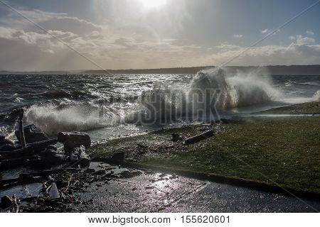 A wave explodes as it hits a sea wall in Des Moines Washington.