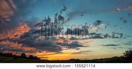 panoramic sunset on cloudy sky over rural landscape