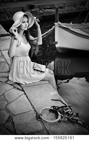 Romantic blonde woman with hat and long hair in port. Blackwhite