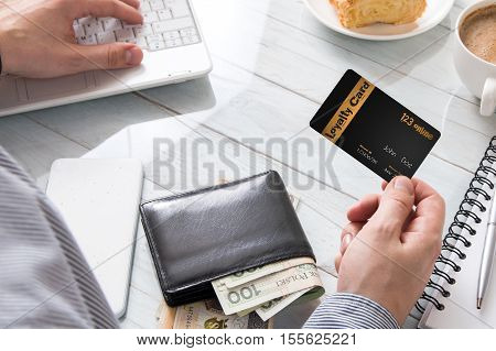 Man uses a loyalty card while online shopping