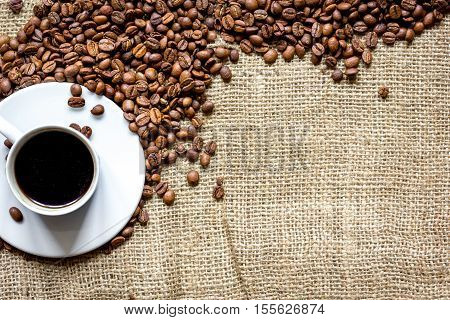 coffee beans with coffe cup on linen cloth background top view. poster