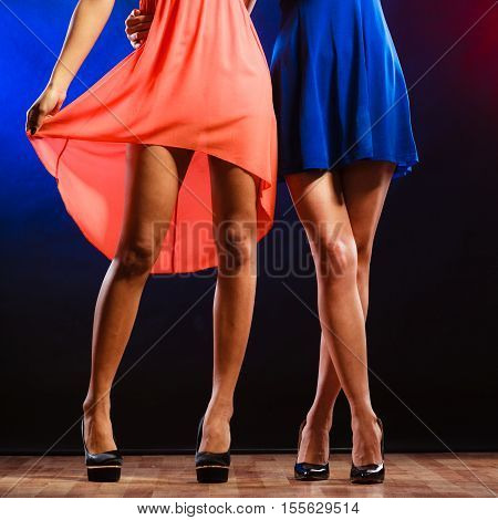 New year celebration disco concept - women in evening dresses dancing in club part of body female legs in high heels on party floor