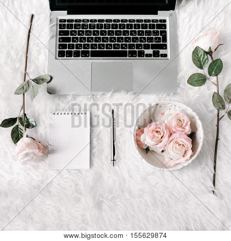 Freelance woman workspace in flat lay style with laptop, vintage tray, roses, notebook and pen on white fur background. Top view, flat lay. Freelance concept.