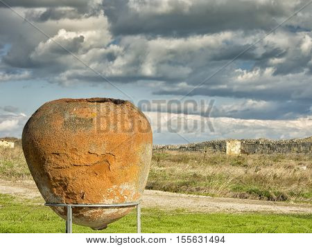 A dramatic blue sky with white clouds over the ruins of an ancient pot - amphorae at Histria, on the shores of Black Sea. Histria is the oldest urban settlement on Romanian territory