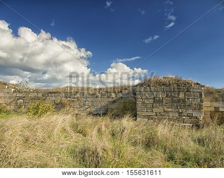 A dramatic blue sky with white clouds over the ruins of the ancient greek colony of Histria, on the shores of Black Sea. Histria is the oldest urban settlement on Romanian territory
