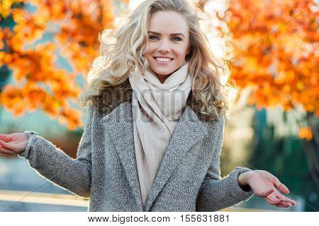 Beautiful smiling cute blonde girl on background of autumn tree. Fashion autumn look