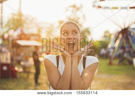 Happiness. Woman in a good mood. Enjoying in life concept. Having fun at funfair.Spending time in a amusement park,summer vacation with friends.Colourful and inspirational,childish spirit.Excited girl