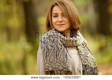 Smiling young caucasian woman in warm autumn coat and stylish tippet on blurred natural background