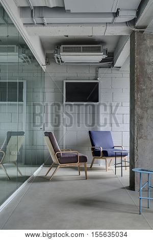 Interior in the office in a loft style with a light brick wall. There are metal round tables and multi-colored armchairs with wooden legs between a concrete column and glass partitions. Vertical.