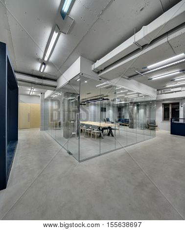 Zone for conference with glass partitions and doors in the office in a loft style. Lamps are glowing. There is a long table and many chairs in the zone. On the back wall there is a relax zone with TV.