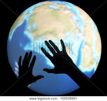 two hands warm on globe concept on a black background