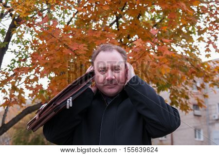 The man covered his ears against the backdrop of an orange maple