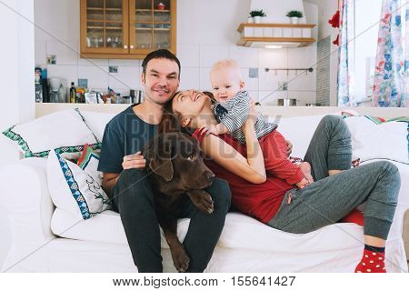 A Young Playful Family At Home On The Couch.