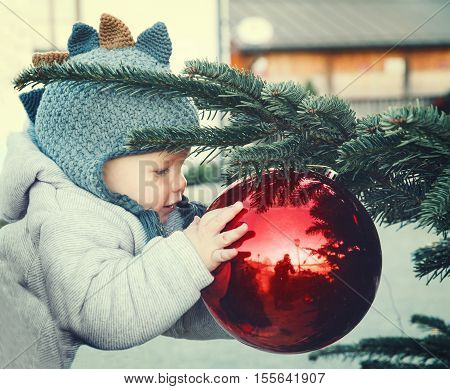 The first Christmas and New Year! Cute baby looking at a reflection in a bowl on a Christmas tree. Holidays Christmas Family concept. Mother and son at winter outdoor among Christmas decorations