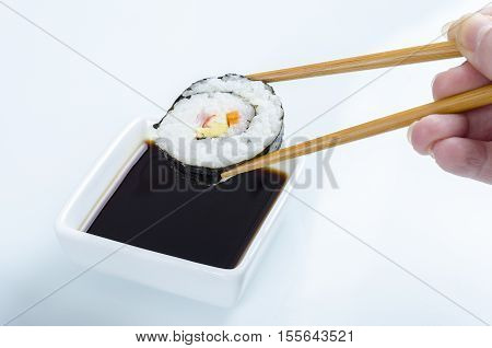 Woman Is Holding A Maki Roll Over Soya.
