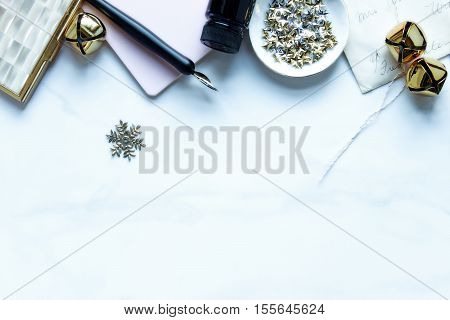 Over head flat lay view of Christmas winter desktop. Gold, pink and white accents. Office supplies and open notebook.