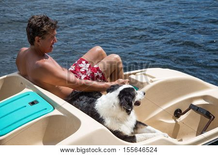 Australian shepherd dog going for a summer ride in a paddle boat with his owner