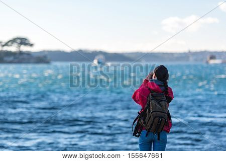 Woman photographer taking pictures of moving boat and harbour. Exploring adventure concept